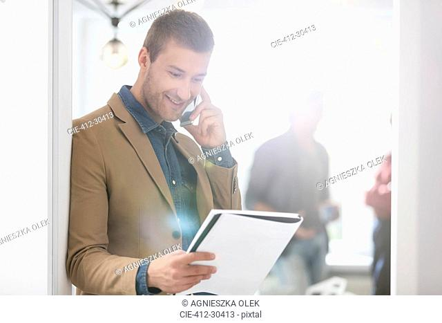 Smiling businessman talking on cell phone and looking down at notebook in office