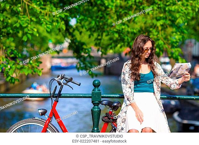 Happy young woman with a city map on bike in european city