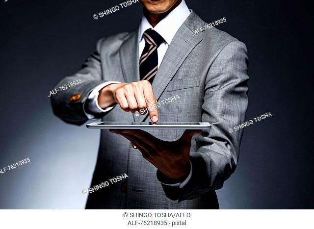 Japanese businessman against grey background