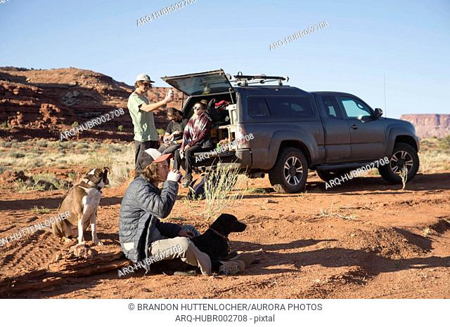 Group of rock climbers with dogs near truck in desert after climb, Moab, Utah, USA