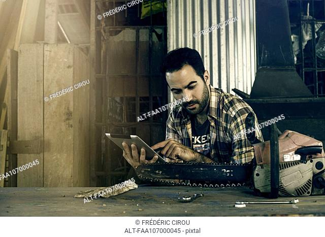 Man searching internet for chainsaw repair instructions