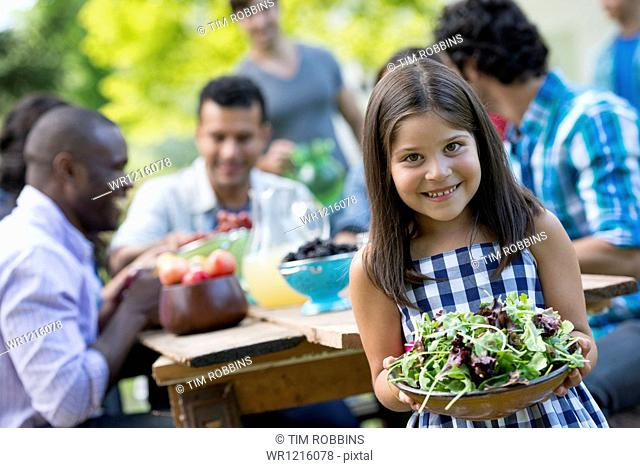 Adults and children around a table in a garden. A child holding a bowl of salad