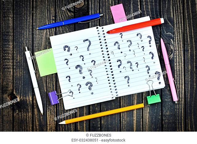 Questions text on notepad and office tools on wooden table