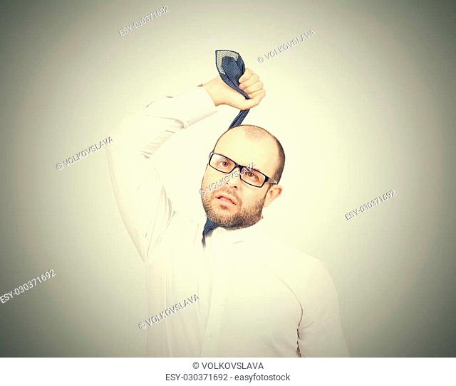 Suicidal businessman strangling himself tie. Isolated on gray background