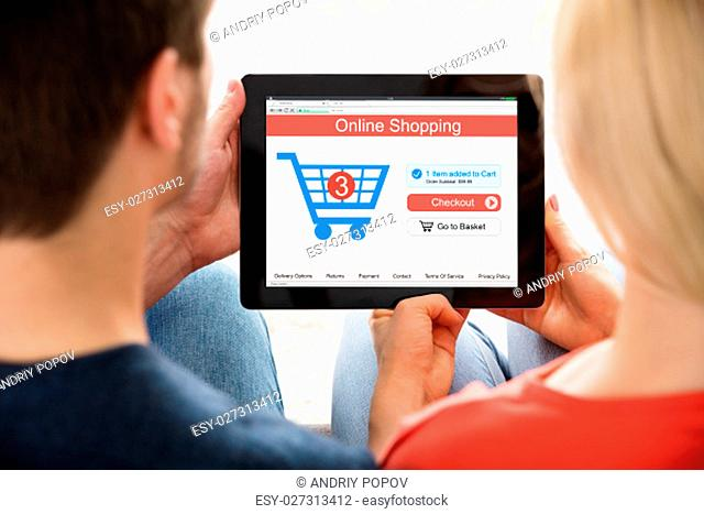 High Angle View Of Couple Sitting In Living Room Shopping Online On Digital Tablet