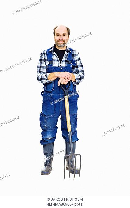 Studio portrait of farmer with pitchfork