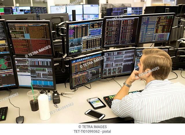 Young trader analyzing computer data