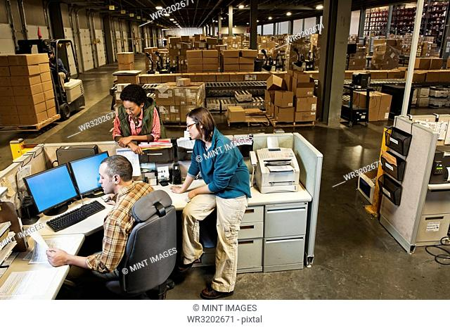 Three mixed race warehouse workers studying a document on a computer at the front desk of a distribution warehouse