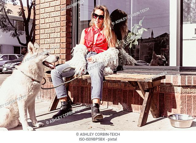 Young woman with pet dog at shopfront