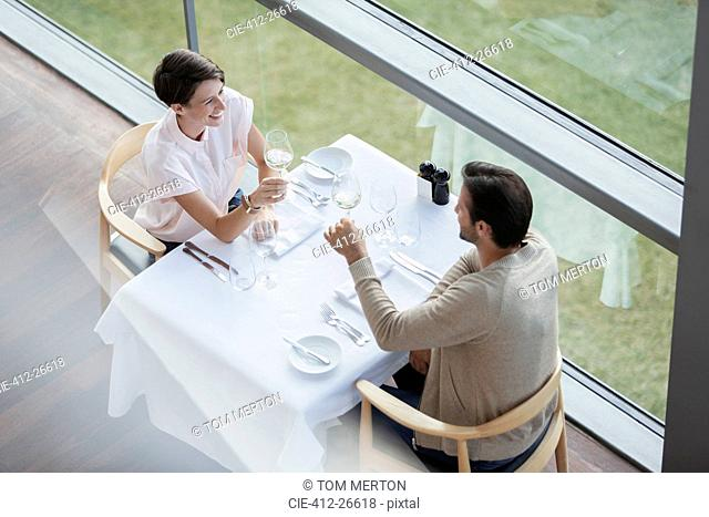 Couple toasting wine glasses at restaurant table at window