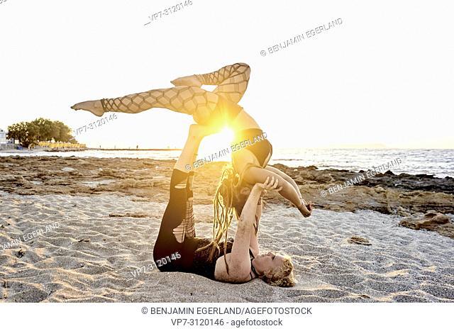 Yoga exercises on beach, Aerial Yoga, in holiday destination Chersonissos, Crete, Greece