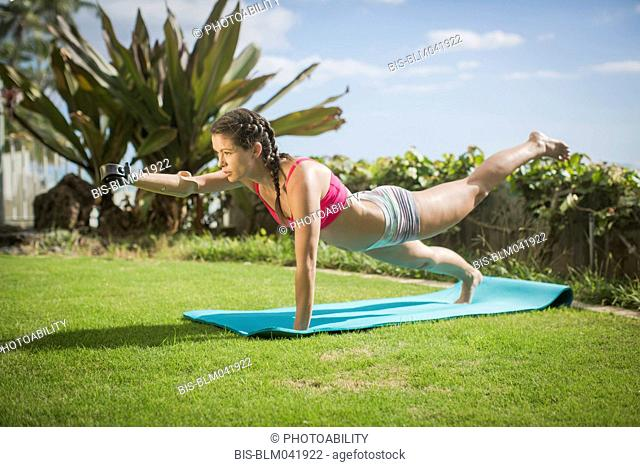 Mixed race amputee practicing yoga in grass