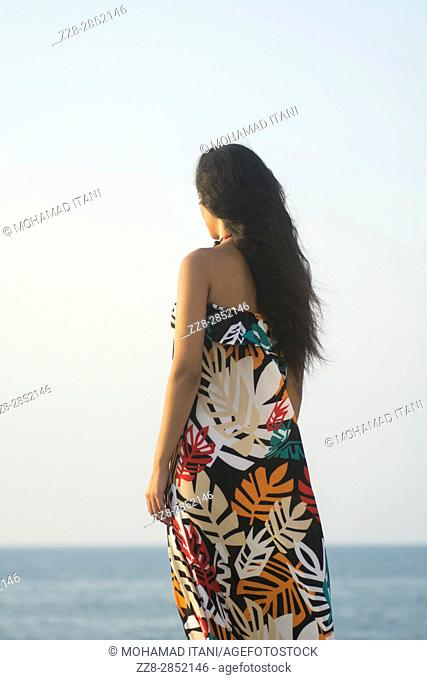 Young woman standing on the beach looking away