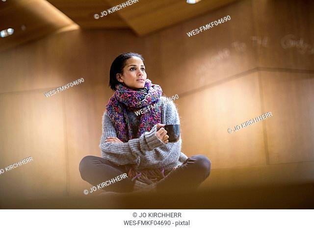Portrait of fashionable young woman with cup of coffee