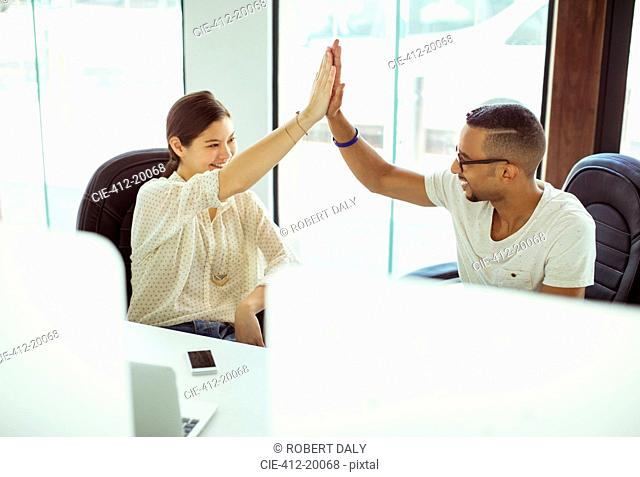 People high fiving in office