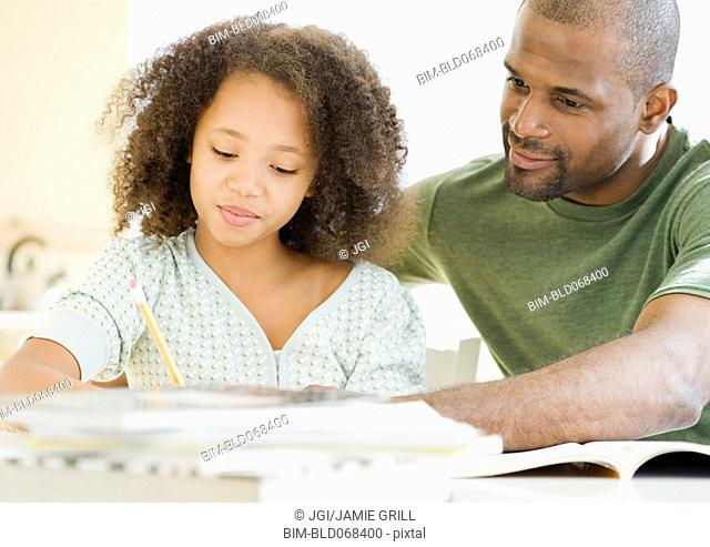 African father helping daughter with homework