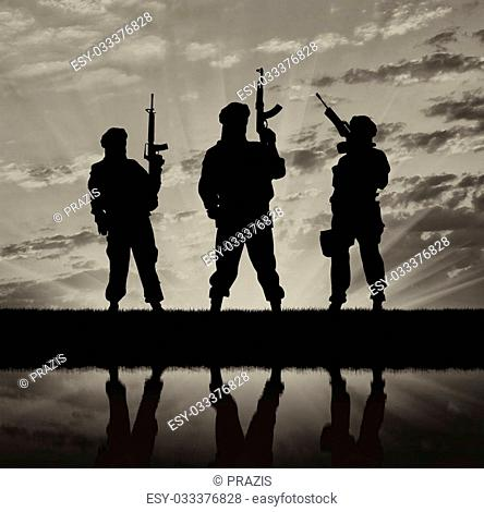 Concept of a terrorist. Silhouette of terrorists with a rifle and a reflection on the water at sunset and reflection