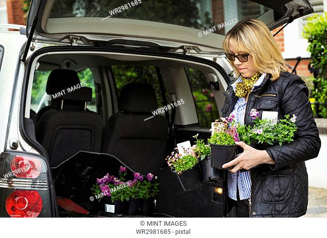 Woman wearing sunglasses standing at back of estate car with open hatch, holding plastic flower pots