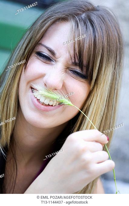 Tickling with a blade of grass young woman portrait