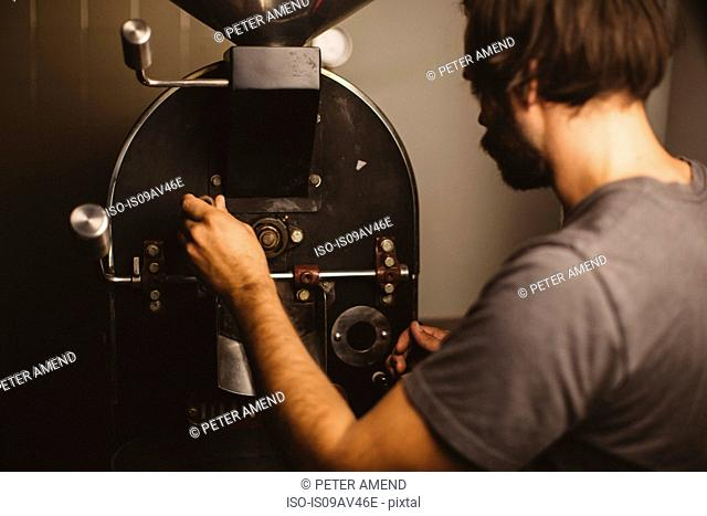 Man pouring coffee beans into coffee roaster, rear view