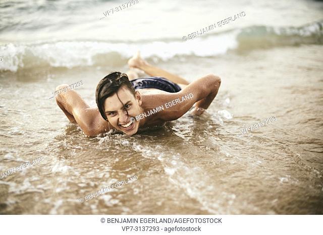 Young man lying on Potamos beach, in holiday destination Malia, Crete, Greece