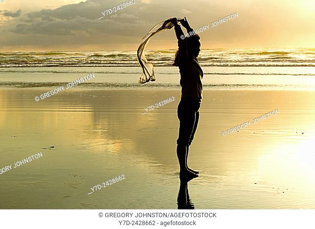 A woman lets a scarf blow in the wind at sunset on the beach in Newport, Oregon