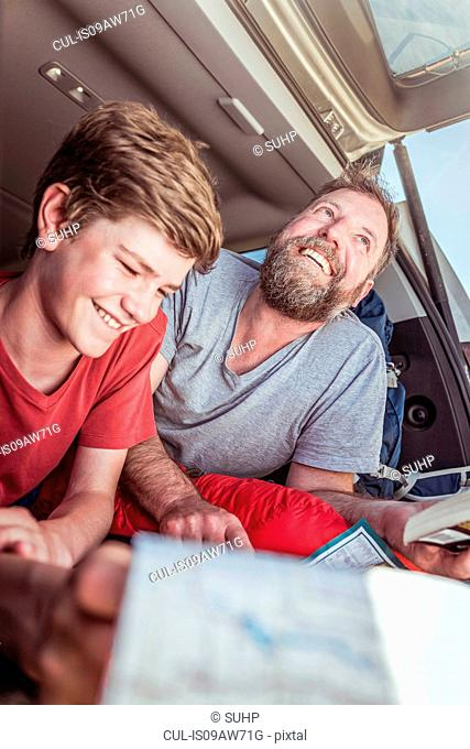 Mature man and teenage son reading map whilst lying in vehicle