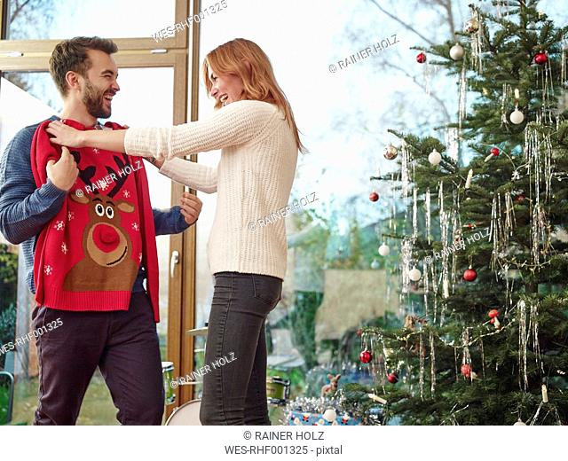 Couple standing in front of Christmas tree trying on Christmas jumper