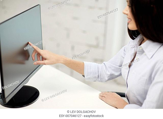business, people, technology and education concept - close up of woman pointing finger to computer monitor in office