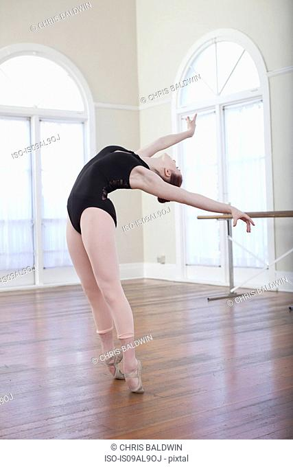 Teenage ballerina leaning back in ballet position at ballet school