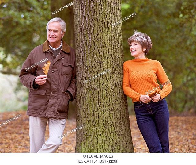 A senior couple leaning against a tree in autumn time