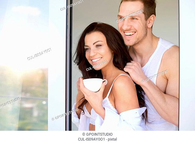 Sexy young woman and boyfriend looking out from bedroom window