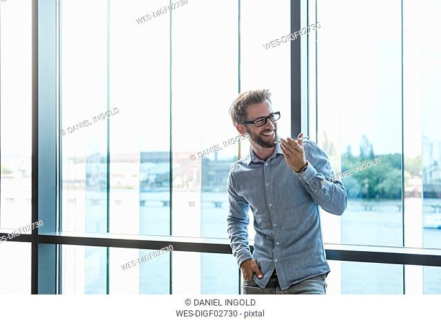 Smiling man using cell phone at the window