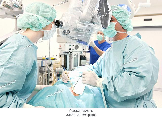 Doctors operating on patient in operating room