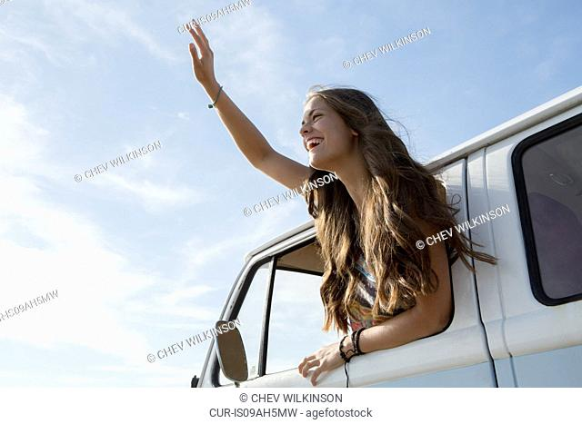 Young woman leaning out of campervan waving
