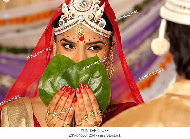 Bengali bride hiding her face from the groom