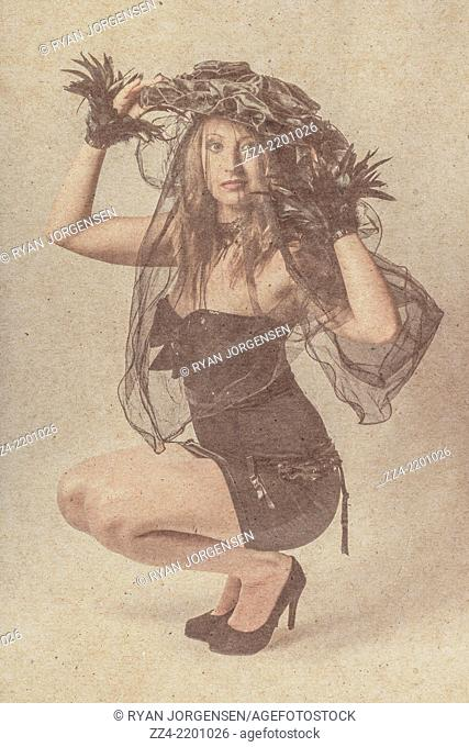 Old style image of a full body blond girl kneeling for a vintage photo in bizarre fashion