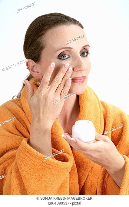 Woman wearing a bath robe, putting on lotion