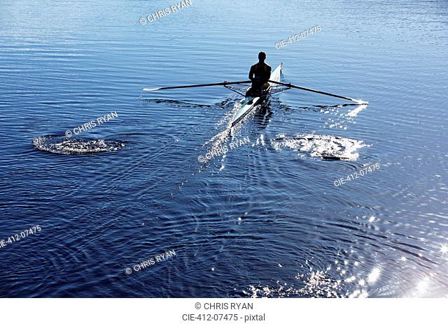 Man rowing scull on lake