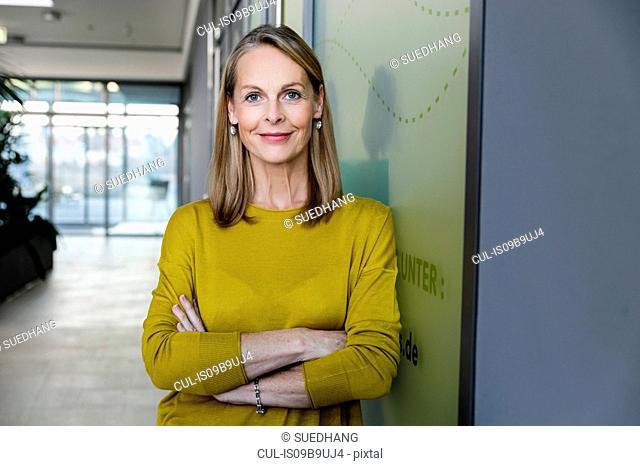 Portrait of confident mature businesswoman in office corridor