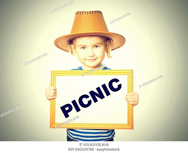 Little Funny girl in striped shirt with blackboard. Text PICNIC. Isolated on white background