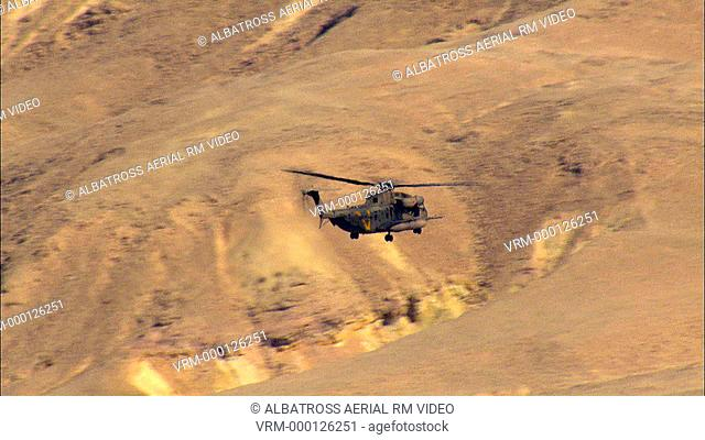Aerial footage of Military Helicopter Flying above the Desert