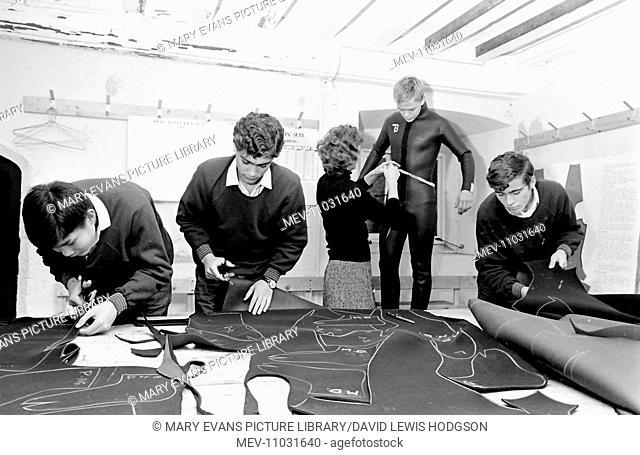 Schoolboys and a teacher at work in a classroom, cutting out material for making wetsuits at Atlantic College (United World College of the Atlantic)