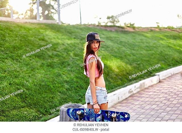 Portrait of young woman standing outdoors, holding skateboard