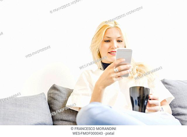 Blond young woman sitting on couch with cup of coffee looking at smartphone