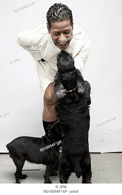 Studio shot of mature woman playing with pet dogs