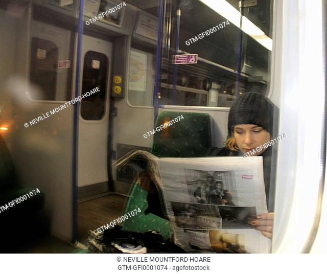 Woman sitting reading a newspaper on an empty train at night
