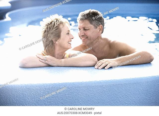 Mature woman and a senior man smiling in a swimming pool