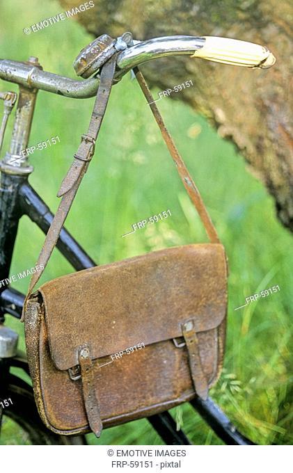 Old leather bag hanging on bicycle handlebar
