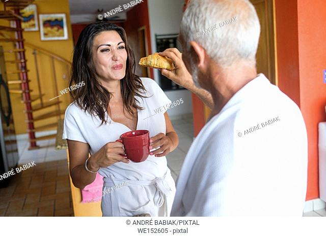 Breakfast of unequal couple - older man feeding a croissant to younger woman, Nuevo Vallarta, Nayarit, Mexico